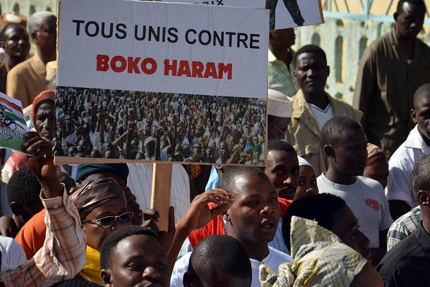 """A person holds a sign reading """"All united against Boko Haram"""" during a protest against deadly raids by Boko Haram on Feb 17, 2015 in Niamey. This week in another attack likely to be by the same group, a teenage girl blew herself up at a crowded bus s"""