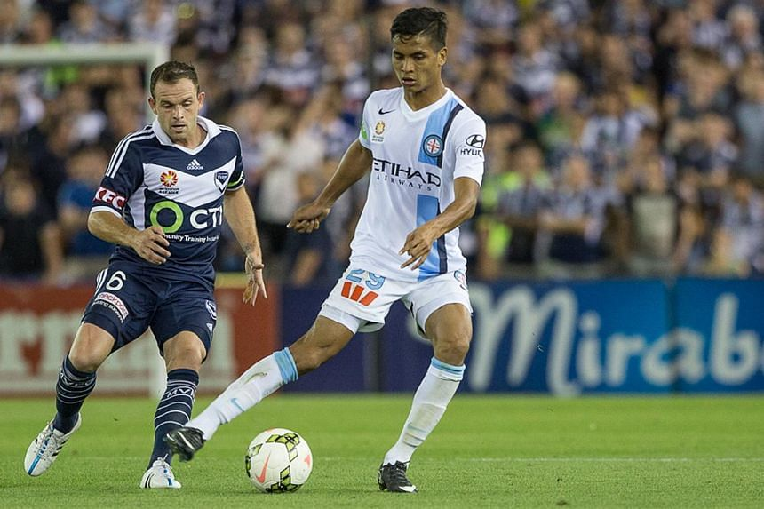 Melbourne City's Singaporean defender Safuwan Baharudin (in white) controls the ball against Melbourne Victory's Leigh Broxham, during his debut in the Australian League at the Etihad Stadium in Melbourne, Australia, on Feb 7, 2015. -- PHOTO: ME