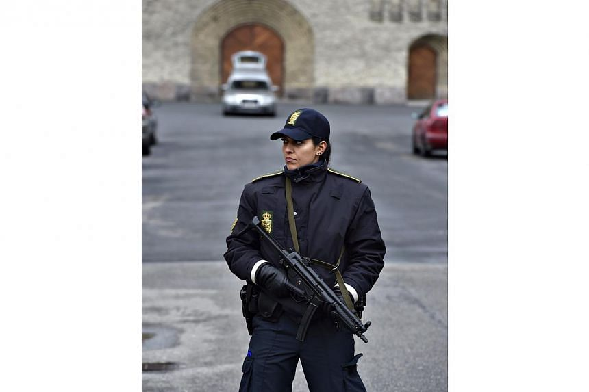 An armed female police officer standing in front of Grundtvigs Kirke (church) in Copenhagen on Feb 24, 2015 where the funeral service for Finn Noergaard is being held.Over 1,000 mourners turned out for the funeral. -- PHOTO: EPA
