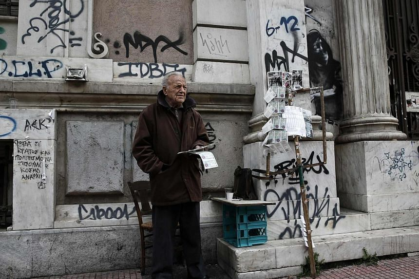 Christos Tzaris, 79, sells lottery tickets outside in central Athens on Feb 24, 2015. International creditors on Tuesday pored over a list of reforms proposed by Greece's new anti-austerity government aimed at securing a four-month extension of