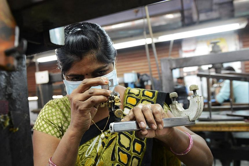 An Indian worker wears a protective mask following an outbreak of swine flu as she works at a diamond polishing factory in the Bapunagar area of Ahmedabad on Feb 20, 2015.An Indian city has banned public gatherings to contain the spread of dead