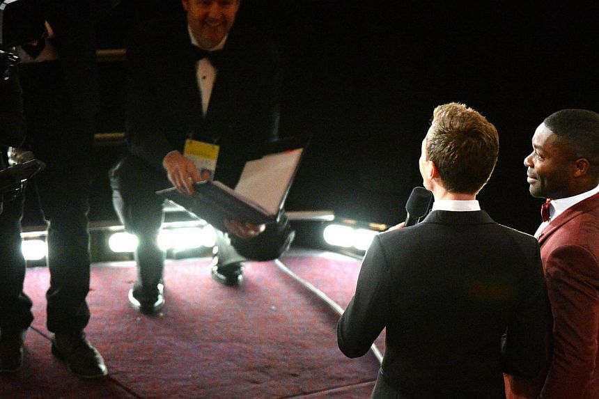 Host Neil Patrick Harris (left)interacts with actor David Oyelowoduring the 87th Annual Academy Awards at Dolby Theatre on Feb 22, 2015 in Hollywood, California. -- PHOTO: AFP
