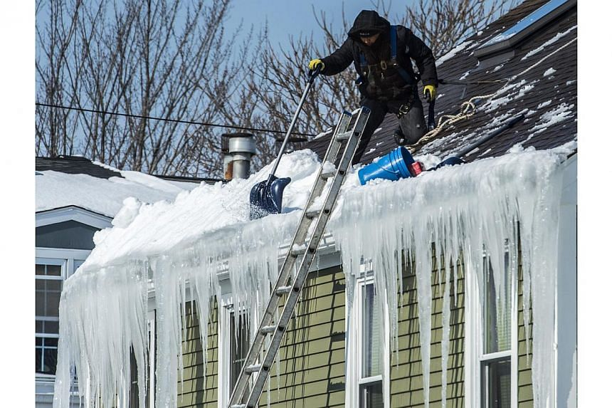 A roofer shovelling snow off a roof in the Dorchester neighborhood of Boston, Massachusetts on Feb 19, 2015. -- PHOTO: EPA