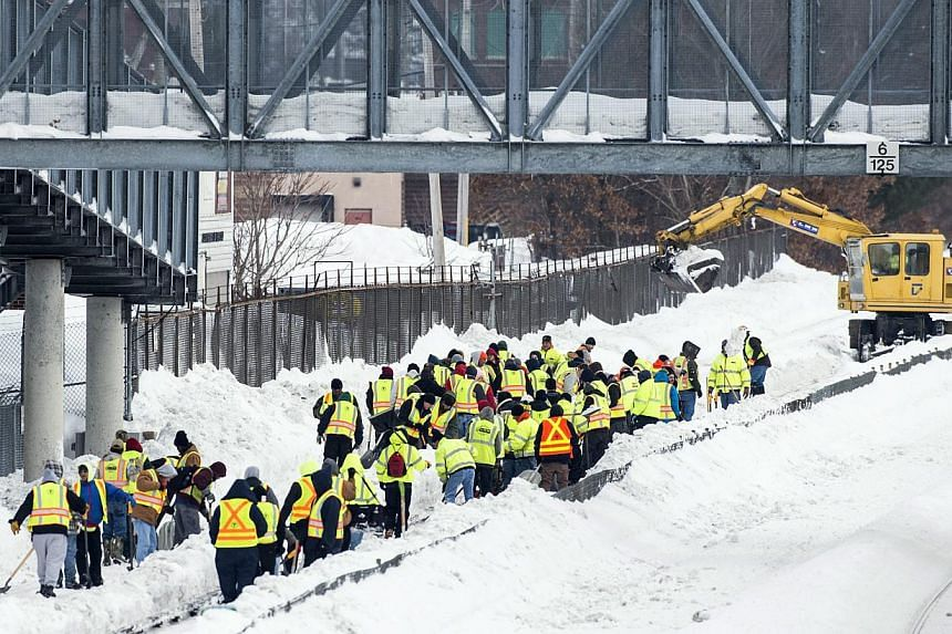 Workers removing snow and ice from Massachusetts Bay Transportation Authority (MBTA) tracks in Quincy, Boston, Massachusetts on Feb 19, 2015. -- PHOTO: EPA