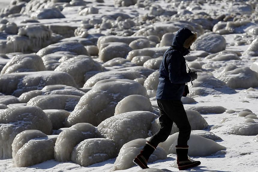 A woman walking past frozen mounds of ice along Lake Michigan in Chicago, Illinois, on Feb 19, 2015. -- PHOTO: REUTERS