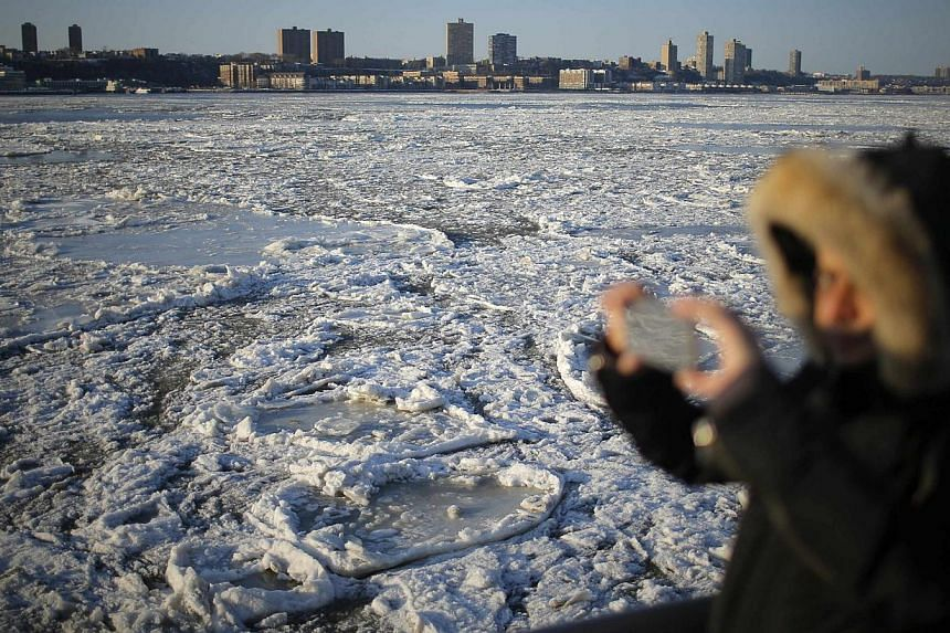 A man taking pictures of ice floes along the Hudson River in New York, on Feb 20, 2015. -- PHOTO: EPA