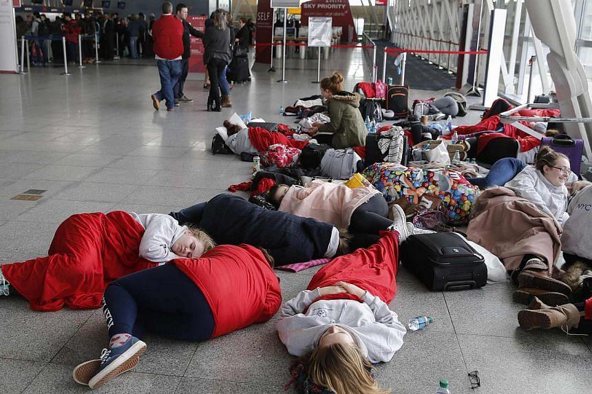 Travelers sleeping in Terminal 4 of JFK International Airport in New York on Feb 22, 2015. -- PHOTO: REUTERS