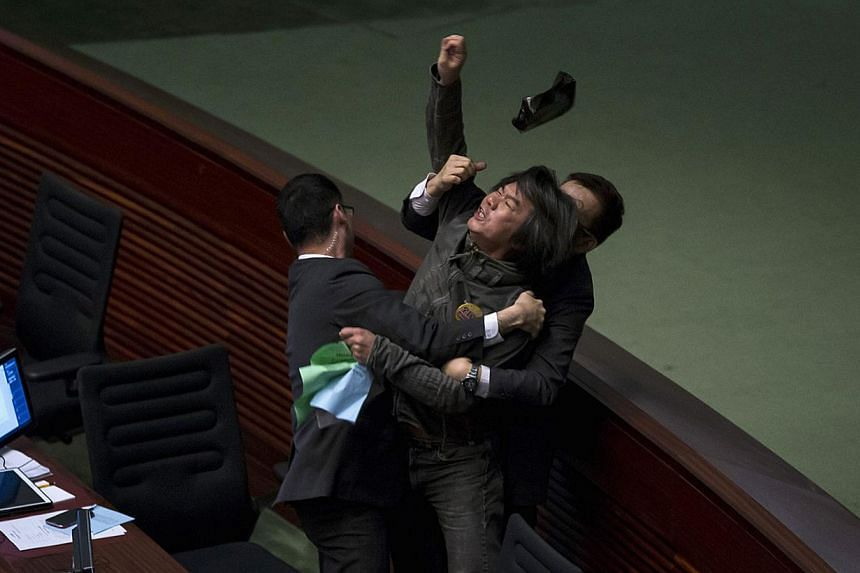 Pro-democracy lawmaker Leung Kwok-hung throws an object at Hong Kong's Financial Secretary John Tsang (not pictured) to demand a universal retirement protection scheme during the annual budget report at the Legislative Council in Hong Kong Feb 25, 20