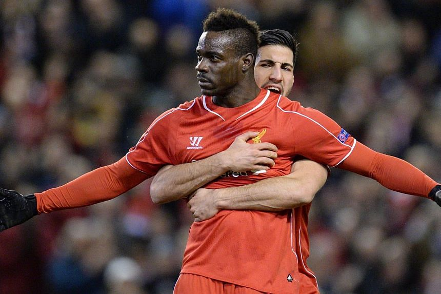 Liverpool's Italian striker Mario Balotelli (front) spreads his arms wide after scoring from the penalty spot for the opening goal as German midfielder Emre Can (back) embraces him from behind during the Uefa Europa League round of 32 first leg footb