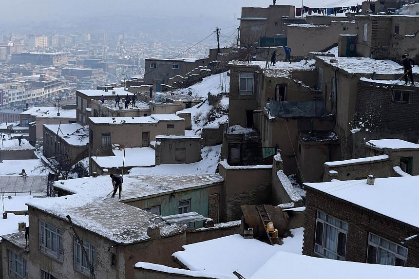 Afghan residents remove snow from the roof of houses overlooking Kabul on Jan 25, 2015. Avalanches triggered by heavy snow have killed more than 100 people in mountainous areas of northern Afghanistan, officials said on Wednesday, as rescuers battled