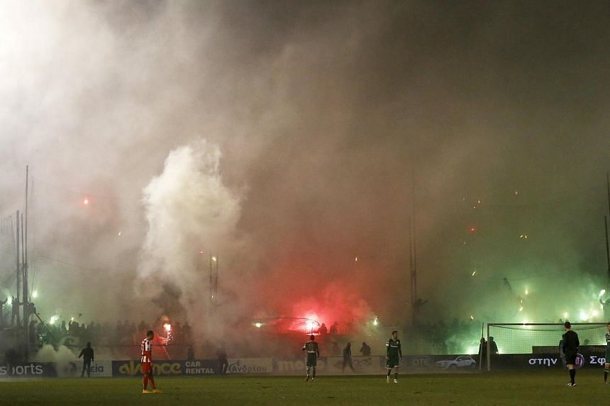 Smoke from flares lit by Panathinaikos' fans rises during the Greek Super League football match between Panathinaikos and Olympiakos at Leoforos stadium in Athens on Feb 22, 2015. -- PHOTO: REUTERS
