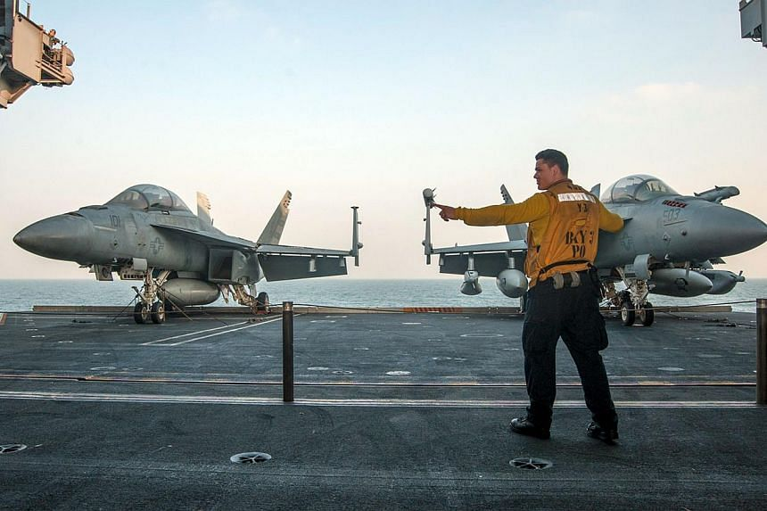 An avaiation handler signals to raise an aircraft elevator from the hangar bay to the flight deck of the aircraft carrier USS Carl Vinson during operations in the Gulf region on Jan 6, 2015.The American public has grown more supportive of the U
