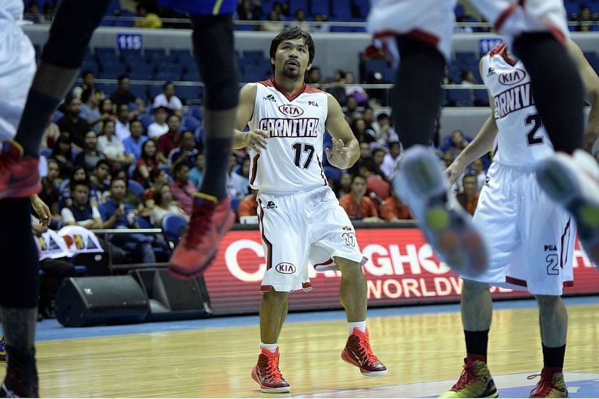 Philippine boxing hero Manny Pacquiao (centre), playing for Kia, looks as players rebound a ball from the basket during a professional basketball game between Kia and Talk and Text in Manila on Feb 25, 2015. Philippine basketball authorities have sac