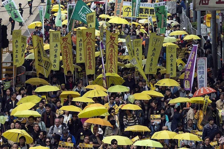 Pro-democracy protesters holding up yellow umbrellas during a march in Hong Kong on Feb 1,2015. The city's economic growth slowed in the fourth quarter as a sluggish global economy and domestic political unrest weighed on spending. -- PHOTO: REUTERS&