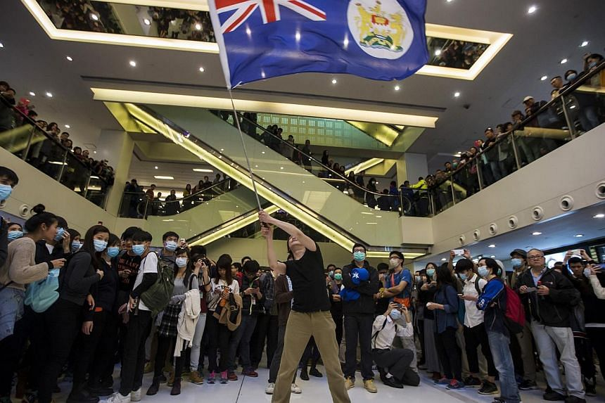 A protester waving a colonial Hong Kong flag during a demonstration inside a shopping mall in Hong Kong on Feb 15, 2015. The city has pledged HK$290 million (S$50.74 million) to help businesses hit by more than two months of pro-democracy protests. -