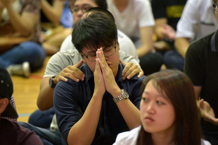 A student clasps his hands while others wait in anxiety during the 2013 GCE A' level results at Pioneer Junior College on March 3, 2014. The 2014 GCE A-Level Examination results will be released on March 2, 2015. -- ST PHOTO: KUA CHEE SIONG