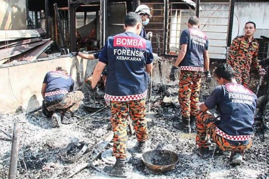 Firefighters sifting through the burnt remains of the house in Serdang. -- PHOTO: THE STAR/ASIA NEWS NETWORK