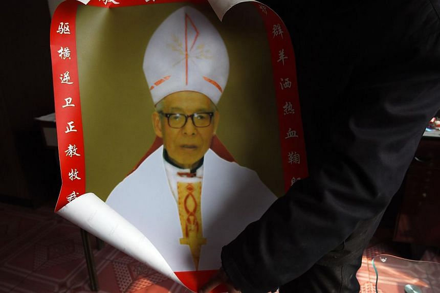 A relative unfurls a photo of Bishop Shi Enxiang at the family home in Shizhuang, in China's northern Hebei province. The family of Chinese underground Catholic bishop Shi Enxiang, who spent more than 50 years in detention for maintaining his loyalty
