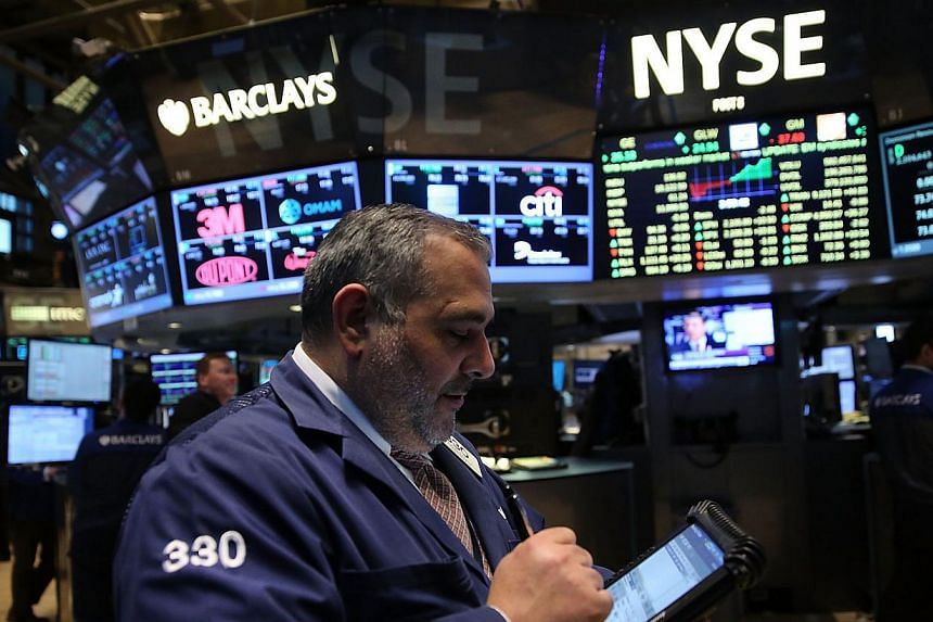 Traders working on the floor of the New York Stock Exchange. The Dow Jones Industrial Average rose 92.35 points, besting Friday's record by about 70 points, and the broad-based S&P 500 inched up to a new all-time close. -- PHOTO: AFP