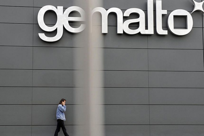 A file picture taken on November 10, 2009 shows an employee walking outside the Gemalto building, the world's leading digital security firm, in Gemenos, southern France.Gemalto NV, the maker of mobile-phone card software, said Wednesday it dete