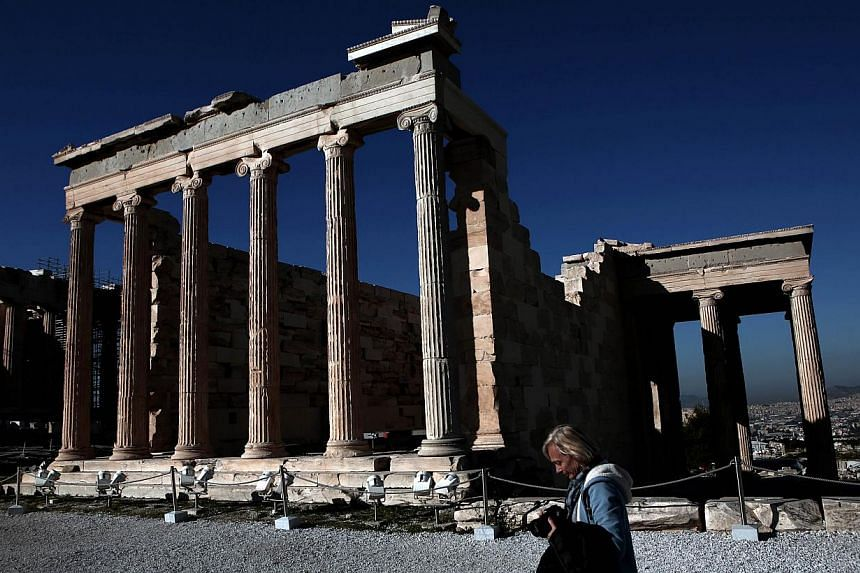 A tourist walks in front of the Erechtheion Temple at the Acropolis hill in Athens on February 21, 2015. The hard work for Greece's new anti-austerity government began Wednesday after it secured an extension to its lifeline financial bailout with p