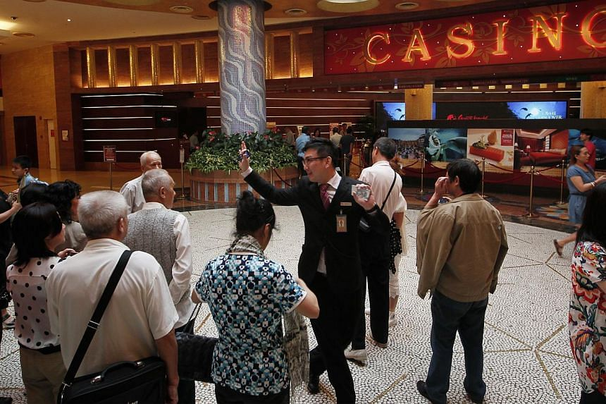 Tourists outside the casino at Resorts World Sentosa. Shares of Genting Singapore slumped to their lowest since May 2010 on Feb 25, 2015, after the casino operator reported a 30 per cent drop in fourth-quarter profit, hurt by poor performance in its