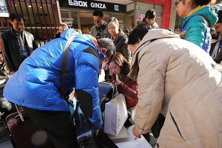 Chinese tourists pack purchases into suitcases outside a store in the Ginza district of Tokyo, Japan. With tensions easing between the two countries, Tokyo is hoping to capitalise on the rising number of Chinese travelling abroad each year. -- PHOTO:
