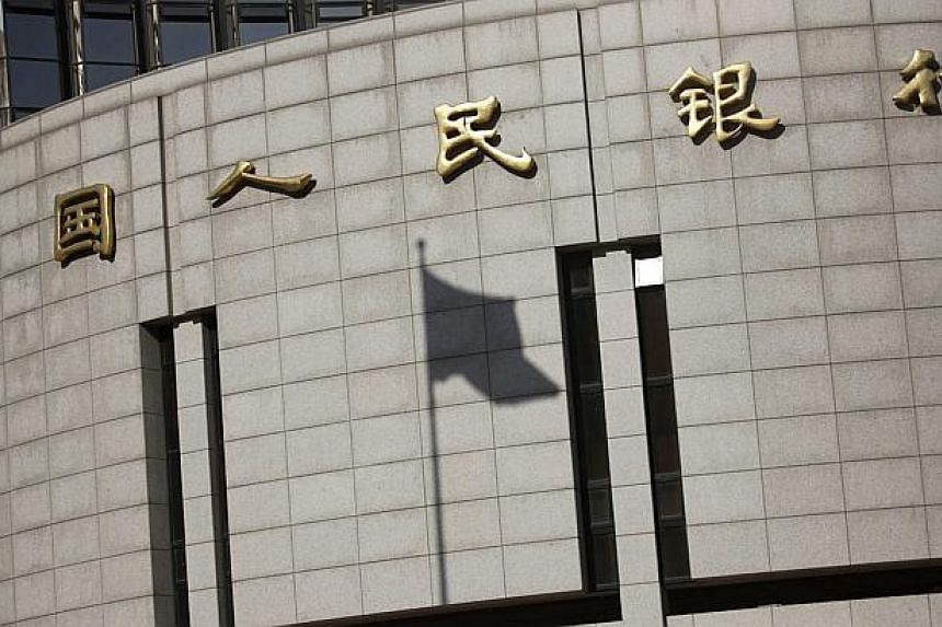A fluttering Chinese national flag casts its shadow on the headquarters of the People's Bank of China, China's central bank, in central Beijing in this Nov 24, 2014 file photo. China is dangerously close to slipping into deflation, the central bank's
