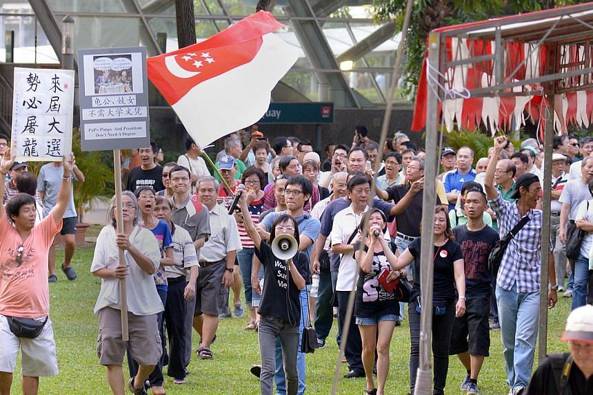 Han Hui Hui (with loudspeaker) and Roy Ngerng (carrying state flag) with supporters at the Return Our CPF rally, marching round the park at the conclusion of the rally, on Sept 27, 2014. Blogger Han Hui Hui has been given until March 25 to decide whe