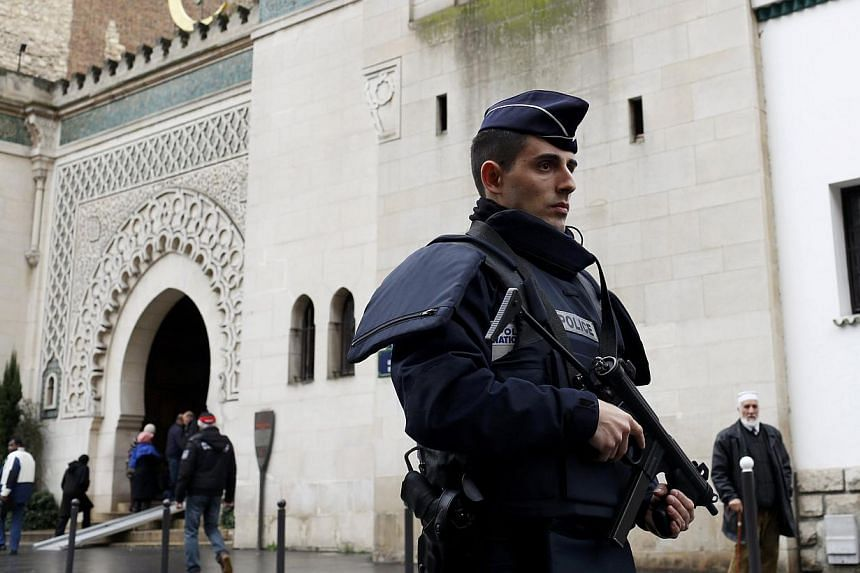 A French policeman stands in front of the entrance of Paris Mosque as French Muslims gather for Friday prayers in Paris on Jan 9, 2015. France outlined plans for a broader dialogue with its Muslim minority on Wednesday after the faith's official