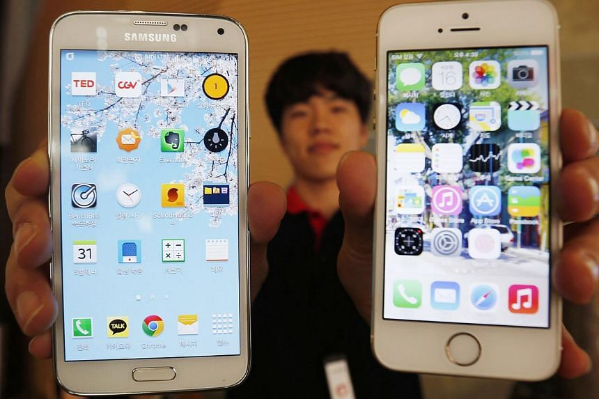A sales assistant holds a Samsung Galaxy S5 smartphone (left) and Apple's iPhone 5  (right) at a store in Seoul in this July 16, 2014 file photo. Google Android dominated the global smartphone market in 2014, holding an 81.5 per cent market