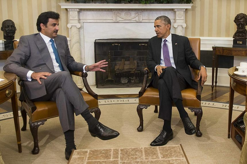 US President Barack Obama (right) and Qatar's emir, Sheikh Tamim Hamad al-Thani, speaking during a bilateral meeting at the White House on Feb 24, 2015. -- PHOTO: AFP