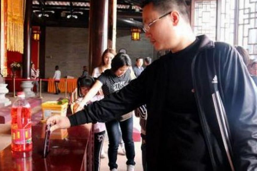 This man was photographed slipping his iPhone 6 into the donation box at a temple in Foshan, Guangdong province on Feb 22, 2015. -- PHOTO: YOUXI.YOUTH.CN