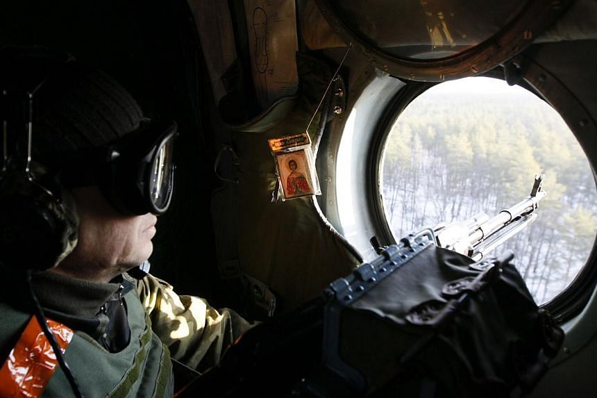 A member of the Ukrainian armed forces keeps his weapon at the ready as he looks out of a helicopter while flying above the Kharkiv region, Feb 24, 2015.-- PHOTO: REUTERS