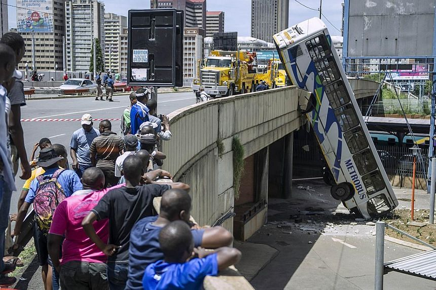 Onlookers gather on Queen Elizabeth bridge to look at a public transport bus that drove over the side of the bridge in Johannesburg, South Africa, on Feb 25, 2015. No fatal injuries were reported and the bus driver sustained minor injuries. -- PHOTO: