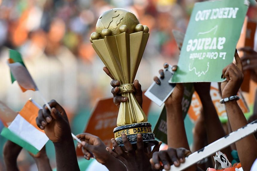 Ivorians hold a replica of the African Cup of Nations trophy as they attend a welcoming ceremony at Felix Houphouet Boigny Stadium to greet their national football team in Abidjan on Feb 9, 2015, a day after Ivory Coast won the 2015 African Cup of Na