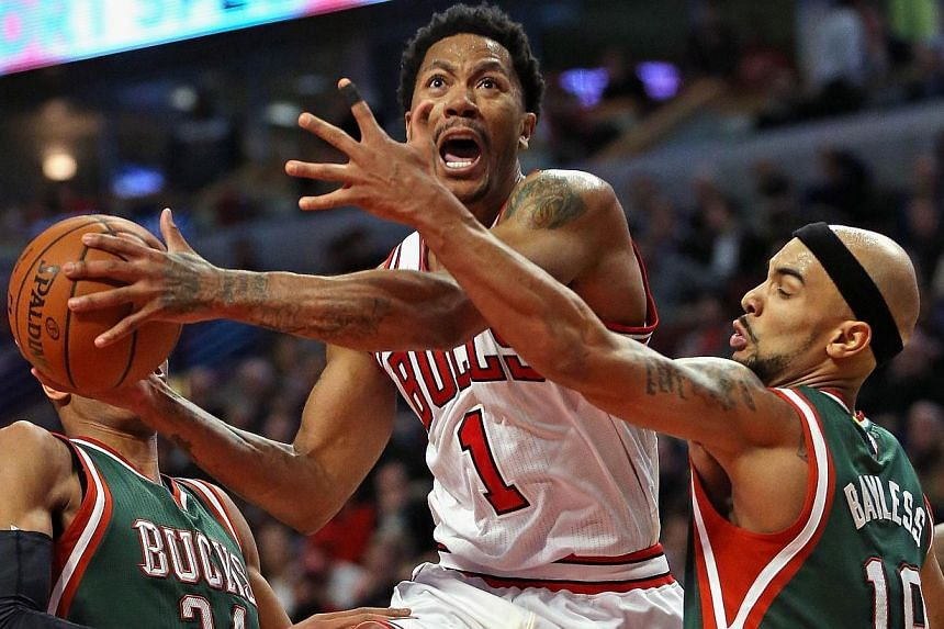 Derrick Rose (#1) of the Chicago Bulls drives between Giannis Antetokounmpo (#34) and Jerryd Bayless (#19) of the Milwaukee Bucks at the United Center on Feb 23, 2015 in Chicago, Illinois. -- PHOTO: AFP