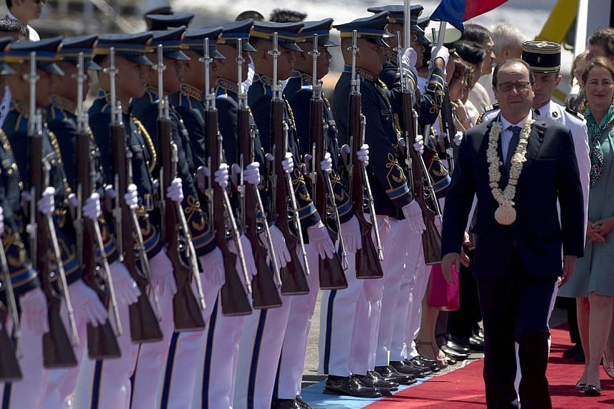 French President Francois Hollande (right) walking past a Philippine honour guard as he arrives at a military airbase in Manila on Feb 26, 2015. -- PHOTO: AFP