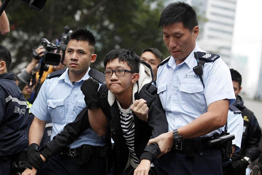 Hong Kong police detain a pro-democracy demonstrator (centre) as police clear the main protest site in the Admiralty district in Hong Kong on Dec 11, 2014. Asia's richest man, Li Ka Shing, said on Thursday, Feb 26, 2015,Hong Kong people would b