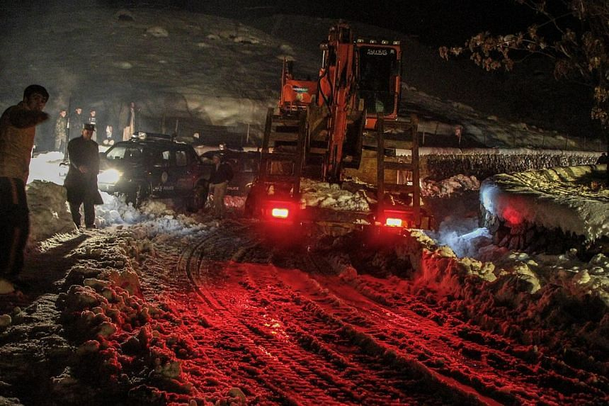 Afghan authorities remove snow from the roads as part of rescue efforts after an avalanche in the Panjshir valley, Afghanistan onFeb 25,2015. More than 200 people have been killed in the series of avalanches triggered by heavy snowfall, o