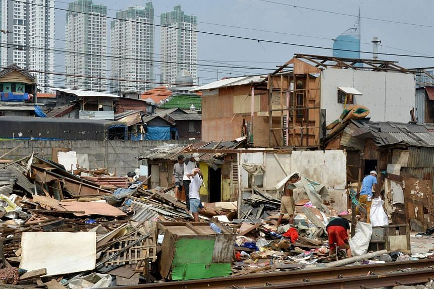 Slum dwellers dismantling their shanty houses along railroad tracks in Jakarta last August. Indonesia's government has failed in multiple attempts to provide housing for its vast low-income population.