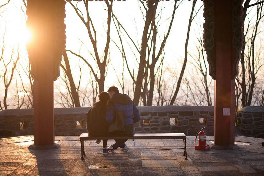 A couple kiss in a pagoda overlooking the Seoul city skyline on Feb 13, 2015. Share price of South Korea's biggest condom maker surged on Thursday, Feb 26, 2015,after the country's highest court struck down a decades-old law banning adultery. -