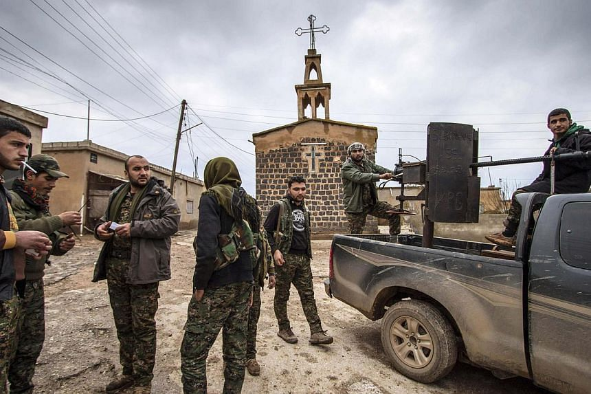 Fighters of the Kurdish People's Protection Units (YPG) stand in front of a church in the Assyrian village of Tel Jumaa, north of Tel Tamr town on Feb 25, 2015. Islamic State in Iraq and Syria (ISIS) militants have abducted at least 220 people f