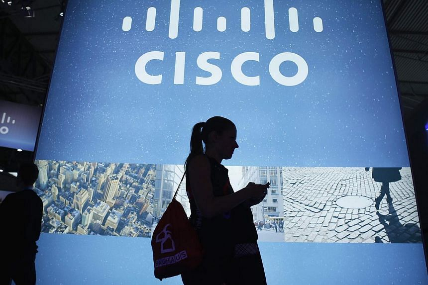 A visitor walks past a Cisco advertising panel as she looks at her mobile phone at the Mobile World Congress in Barcelona in this February 27, 2014 file photo. United States network equipment maker Cisco Systems has been the chief casualty of China's