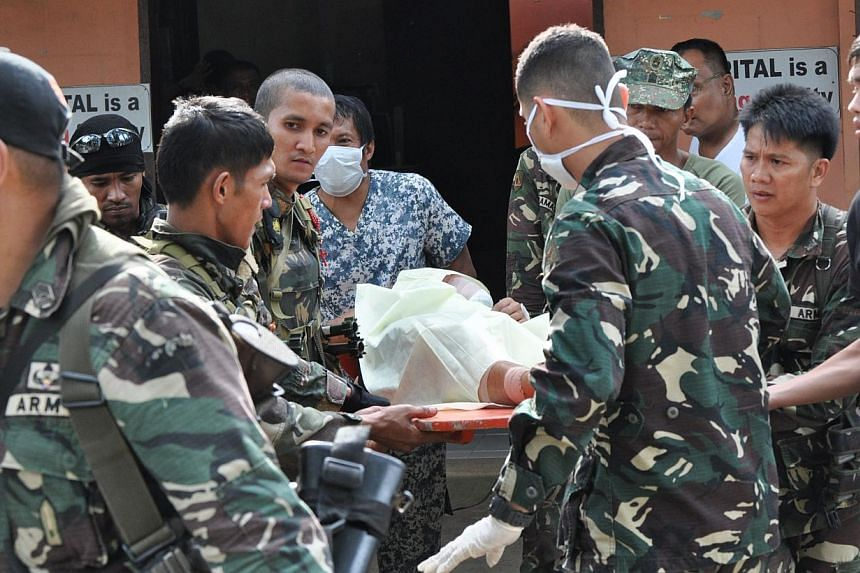 Philippine soldiers evacuating a wounded comrade, after clashes with Abu Sayyaf fighters on the southern island of Mindanao on Feb 25, 2015, to a nearby military hospital in Zamboanga City. -- PHOTO: AFP