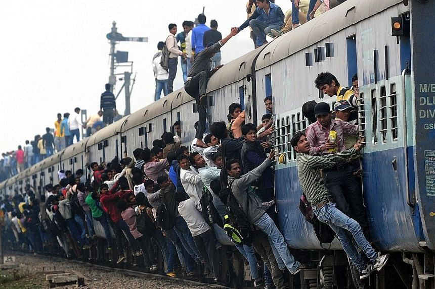Passengers hanging onto a train as it departs from a station on the outskirts of New Delhi on Feb 25, 2015. -- PHOTO: AFP