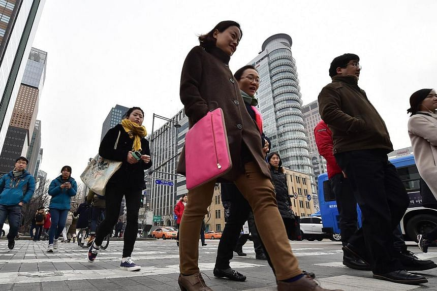 Pedestrians crossing an intersection in the business district in Seoul on Jan 14, 2015. -- PHOTO: AFP