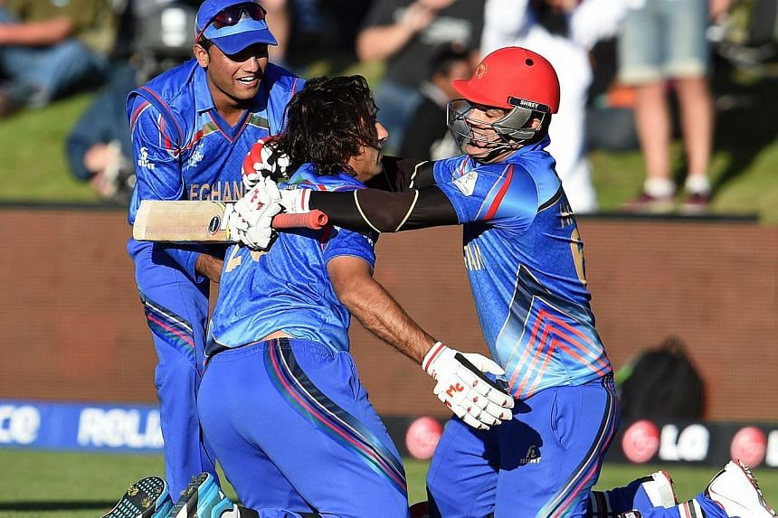 Afghanistan batsman Shapoor Zadran (centre) celebrates with teammate Hamid Hassan (right) after hitting the winning runs to defeat Scotland as reserve Usman Ghani (left) looks on in their 2015 Cricket World Cup Group A match in Dunedin on Feb 26, 201