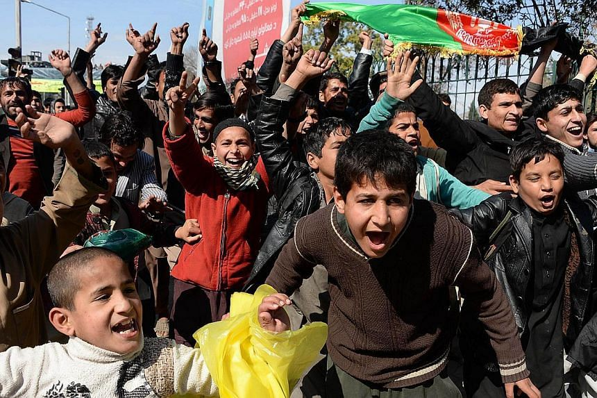 Afghan cricket fans watch the live television broadcast of their national cricket team victory in the World Cup 2015 match between Afghanistan and Scotland, in Jalalabad capital of Nangarhar province on Feb 26, 2015. Six people were injured after ecs