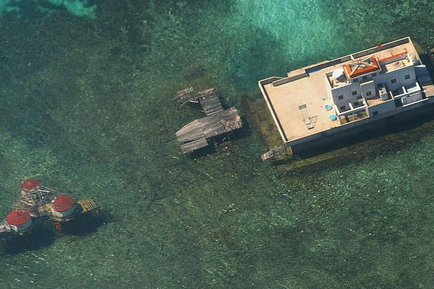 "An aerial photograph taken from a Philippine Air Force aircraft on Nov 6, 2003 showing Chinese-built structures on the Mischief Reef in the disputed Spratly islands. China is conducting ""large scale"" land reclamation and construction on a reef i"